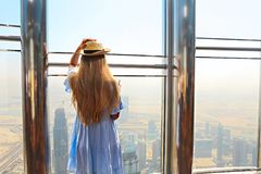 Girl tourist with mobile phone by the window of skyscraper of th. E Burj Khalifa in Dubai, United Arab Emirates, UAE royalty free stock images