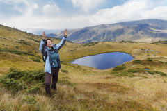 Girl tourist in the mountains emotionally gesticulates Stock Photo