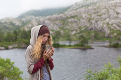 Girl the tourist in mountains heated a mug of warm tea. Pretty girl the tourist in mountains heated a mug of warm tea Royalty Free Stock Image