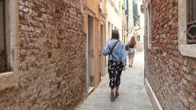 Girl tourist is on a narrow ancient street in Venice, Italy. Traveler walks in Venice.