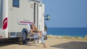 Girl tourist near her trailer on parking near sea.