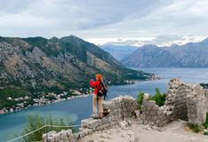 Girl tourist photographs the Bay of Kotor from the fortress wall Royalty Free Stock Image