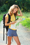Girl tourist at a puzzlement. Standing  a map in hand Stock Image