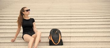 Girl tourist relaxing on stony stairs near her backpack. Take minute to relax. Woman sunglasses stylish black outfit. Walking Paris. Vacation and travel concept stock photo