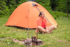 Girl tourist sitting near tent Stock Images