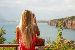 Girl tourist with smartphone taking pictures of seashore Stock Photos