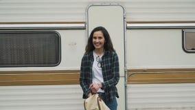 Girl tourist smiling near the travel trailer stock video