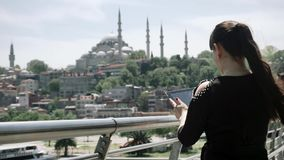 Girl tourist stands and takes pictures on the tablet beautiful sights of the city. Turkey stock footage