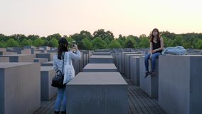 Girl tourist takes pictures of a girlfriend who sits on gray slab, Holocaust Memorial