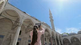Girl tourist taking pictures of the beautiful architecture of the mosque in Turkey stock video