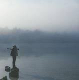 Girl tourist in thick fog on the lake enjoying life. Stock Photo