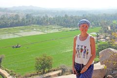 Girl tourist at the top of a mountain, in the background of green rice fields in Hampi.  royalty free stock images