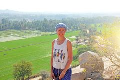 Girl tourist at the top of a mountain, in the background of green rice fields in Hampi.  stock photos