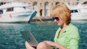 Woman tourist uses a laptop on the background of the urban landscape with yachts. Girl tourist uses a laptop on the background of the urban landscape with yachts stock footage