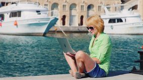 Woman tourist uses a laptop on the background of the urban landscape with yachts. Girl tourist uses a laptop on the background of the urban landscape with yachts stock video footage
