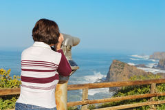Girl tourist watching a sea landscape from the telescope. Stock Photos