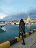 The girl tourist on the waterfront in the sea port Sochi. Girl tourist looking at the yachts in Sochi sea port, evening walk Royalty Free Stock Images