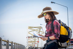 Girl tourists read the map on the bridge. Travel Royalty Free Stock Image
