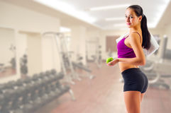 Girl with towel and apple at gym club Royalty Free Stock Image