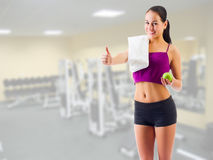 Girl with towel and apple at gym club Royalty Free Stock Photography