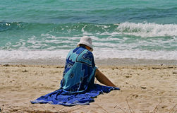 Girl with towel on beach Stock Image
