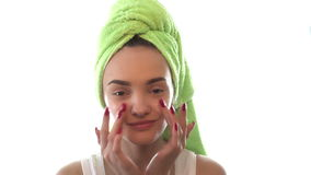 Girl with towel on the hair with both hands causes the cream on her face stock video