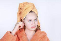 Girl with towel on his head cleaning ears with cotton swab. Royalty Free Stock Image