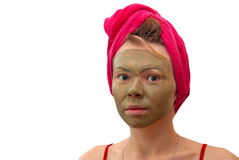 Girl in a towel and a mask. Girl with a red towel on a head and a cosmetic mask on the face Royalty Free Stock Photos