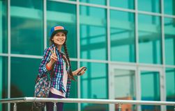 Girl in town. Girl in a cap with a backpack on the background wall of glass Royalty Free Stock Images