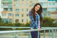 Girl in town. Haired girl with her hair in a checkered shirt on the background of a multistory building. Youth style Stock Photography