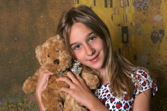 Girl with toy. Bear on color background Royalty Free Stock Photo