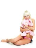 Girl with a toy. Pretty young blond woman wearing pink underwear and embracing a toy Stock Photos