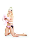 Girl with a toy. Pretty young blond woman wearing pink underwear and embracing a toy Stock Images