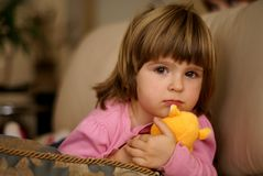 Girl with a toy. Three years old girl laying down on sofa, holding a toy Stock Photo
