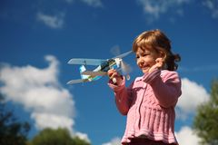 Girl with toy airplane in hands outdoor Stock Photo