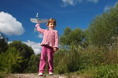 Girl with toy airplane in hands outdoor Royalty Free Stock Photo