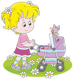 Girl with a toy baby buggy Royalty Free Stock Image