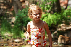 A Girl with a Toy Boat. This four-year-old pixie just loves showing off her new swimsuit and playing with her homemade boat down at the creek Royalty Free Stock Images