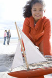 Girl (5-7) with toy boat on beach, smiling, portrait Stock Photo