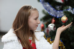 Girl and toy on Christmas tree Royalty Free Stock Photography