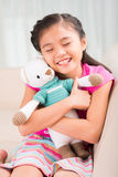 Girl with toy. Cute Asian little girl embracing tight her favorite toy Stock Photo