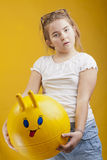 Girl with a toy face ball Royalty Free Stock Image