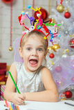 Girl with a toy fireworks on the head draws a congratulatory New Years card Stock Image