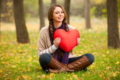 Girl with toy heart at autumn park. Royalty Free Stock Images