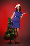 Girl with toy heart near christmas tree Royalty Free Stock Image