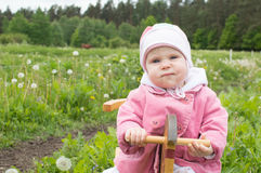 Girl on a toy horse in a field Royalty Free Stock Image