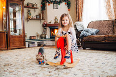 Girl on a toy horse at home Stock Image