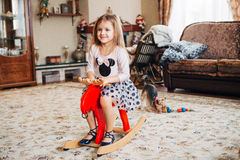 Girl on a toy horse at home Royalty Free Stock Photography