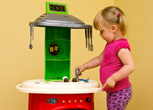 Girl and toy kitchen. Cute two year old girl playing with toy kitchen Stock Images