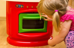 Girl and toy kitchen Stock Image
